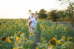 Vati mit dem Sohn, der auf einem Gebiet von Sonnenblumen umarmt Sohnumarmung sein Vater auf einem Gebiet von Sonnenblumen stockbild