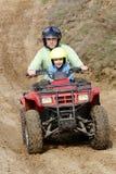 Vati mit dem Sohn, der eine vierfache Leitung reitet Stockfotografie