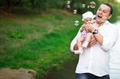 Vati mit der Tochter, die in der Natur spielt stockfoto