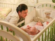 Vati mit einem Baby in einer Krippe Lizenzfreie Stockfotos