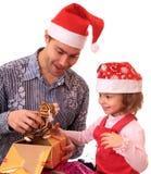 Vati mit geöffneten Geschenken der Tochter. Lizenzfreies Stockfoto