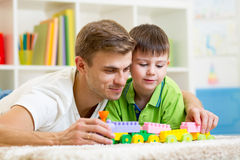 Vati mit Kindersohnspiel zusammen Stockbild