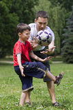 Vati mit seinem Sohn, der Fußball spielt stockbild