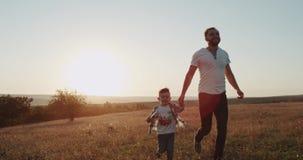 Vati mit seinem Sohn, der an der Natur, irgendeinen Fahrpreis weg schauend, erstaunlicher Sonnenuntergang des Hintergrundes läuft stock footage