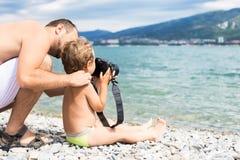 Vati mit seinem Sohn fotografierte Meer Stockbild