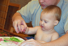 Vati mit seinem Sohn malt Fingerfarben auf Weißbuch Vati unterrichtet sein Kind Sie malen verschiedene Farben Stockfotografie