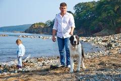 Vati mit seiner kleinen Tochter und einem Hund, der auf den Strand geht Lizenzfreie Stockbilder