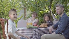 Vati, Mutter und ihre zwei Kinder, die an einem Tisch, das Mittagessen im Garten essend einen sonnigen Tag genießend sitzen Famil stock video