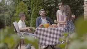 Vati, Mutter und ihre zwei Kinder, die an einem Tisch, das Mittagessen im Garten essend einen sonnigen Tag genießend sitzen Frau  stock video