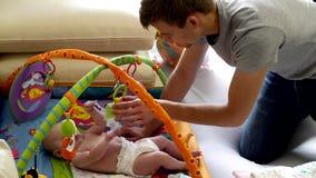 Vati setzt seine kleine Tochter auf eine sich entwickelnde Matte