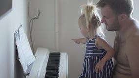 Vati spielt das Klavier mit seiner kleinen Tochter stock footage