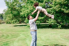 Vati spielt mit seiner Tochter wirft sie oben und fängt Stockbilder