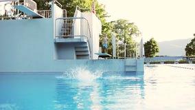 Vati stellt dar, dass Sohn in Pool im Freien springen stock video