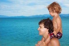 Vati tragen Kind auf Schultern stockbild
