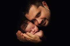 Vati umarmt sein neugeborenes Baby Vater's-Liebe Nahaufnahmeporträt auf einem schwarzen Hintergrund Lizenzfreie Stockfotografie