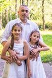 Vati umarmt seine Töchter stockbild