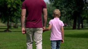 Vati- und Jungenhändchenhalten, glückliche Familie weg gehen, Erziehnung und Freundschaft stockfotografie