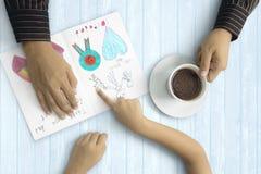 Vati- und Kinderhände mit Grußkarte Lizenzfreies Stockfoto