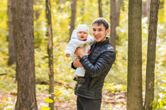 Vati und neugeborene Tochter, die im Park im Herbst spielen Lizenzfreie Stockfotos