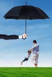 Vati und sein Junge, die unter Regenschirm am Feld spielen Lizenzfreie Stockfotos
