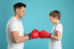 Vati und sein Sohn mit Boxhandschuhen stockbild