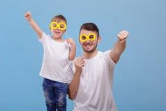 Vati und sein Sohn setzten ihre Gläser auf einen Stock auf einem blauen Hintergrund stockbild