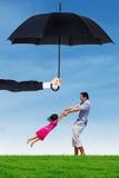 Vati und seine Tochter, die unter Regenschirm am Feld spielen Stockbild