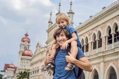 Vati und Sohn auf Hintergrund von Sultan Abdul Samad Building in Kuala Lumpur, Malaysia Reisen mit Kinderkonzept stockfoto