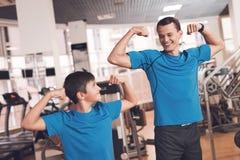 Vati und Sohn in der gleichen Kleidung in der Turnhalle Vater und Sohn führen einen gesunden Lebensstil stockbilder