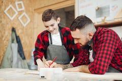 Vati und Sohn in der Werkstatt, die ein Modell einer hölzernen Fläche entwerfend spielt lizenzfreie stockfotografie