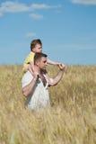 Vati und Sohn, die auf dem Gebiet gehen Stockfotografie