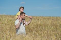 Vati und Sohn, die auf dem Gebiet gehen Lizenzfreies Stockbild