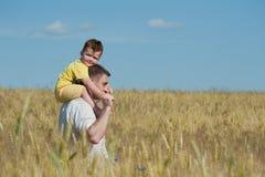 Vati und Sohn, die auf dem Gebiet gehen Lizenzfreie Stockfotos