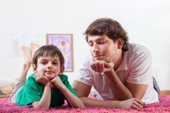 Vati und Sohn, die auf Teppich stillstehen stockbilder