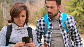 Vati und Sohn, die den besten Fußweg für das Wandern wählen stock video footage