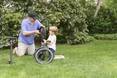 Vati und Sohn, die ein Fahrrad reparieren Lizenzfreies Stockfoto
