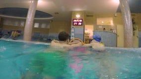 Vati und Sohn, die im Innenswimmingpool baden stock video footage