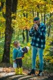 Vati und Sohn im Herbst parken das Spiellachen Zeigen des kranken Vaters, der am Herbstpark niest Kalte Grippe-Saison, laufende N stockbild