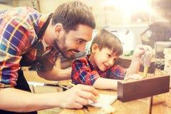 Vati und Sohn mit messender Planke des Machthabers an der Werkstatt Stockfoto