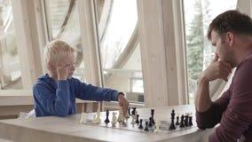 Vati und Sohn spielen Schach in einem Schachverein stock video