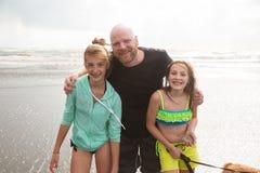 Vati und Töchter am Strand Stockfotografie