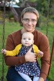 Vati und Tochter auf Schwingen stockfotografie