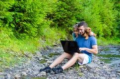Vati und Tochter betrachten den Laptop und sitzen auf dem natur Lizenzfreies Stockfoto