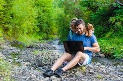 Vati und Tochter betrachten den Laptop und sitzen auf dem natur Stockfotografie