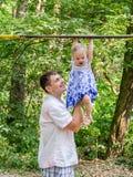 Vati und Tochter, die im Park auf einem Hintergrund von Bäumen, dem Baby hängen an der horizontalen Stange und dem Vater ihres su Lizenzfreie Stockbilder