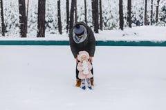Vati und Tochter, die mit schneebedecktem Kiefernwald gehen lizenzfreie stockbilder