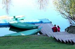 Vati und Tochter sitzen auf der Flussbank nahe der Bootsstation lizenzfreie stockfotografie