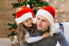 Vati und Tochter, Weihnachtshut, Baum, Geschenkbox stockbild