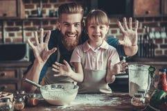 Vati- und Tochterkochen stockbilder