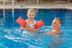 Vati- und Tochterschwimmen im Pool und sie lacht heraus lautes und s lizenzfreies stockfoto